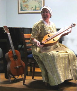 Diane Taraz, Director of the Colonial Singers, displaying the dulcimer, one of the typical musical instruments used in the 1700's.